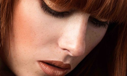 Red haired woman with freckles looking down (sensual look)